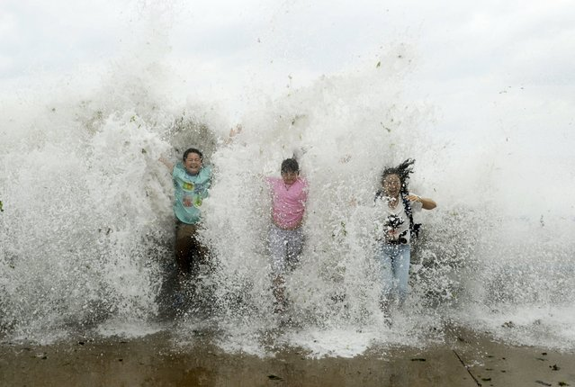 Tourists standing near the sea shore are hit by a wave, which surged past a barrier under the influence of Typhoon Chan-hom, in Qingdao, Shandong province, China, July 12, 2015. (Photo by Reuters/Stringer)