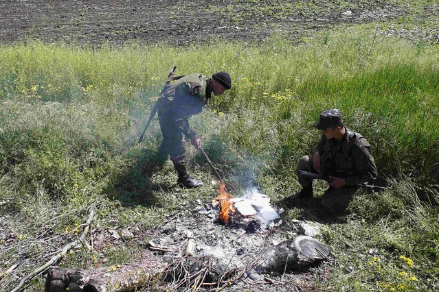 Ukrainian soldiers burn referendum ballot slips that they said were falsified and seized from a car at a checkpoint in Mariupol, on May 11, 2014. Many observers said the referendum lacks credibility, that names were checked against a 2012 voters' list but that anyone who turned up with a passport was allowed to vote, even if they weren't on the list. (Photo by Marko Djurica/Reuters)