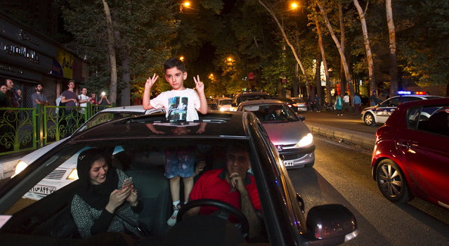 A boy gestures as Iranians celebrate in the streets following a nuclear deal with major powers, in Tehran July 14, 2015. (Photo by Reuters/TIMA)