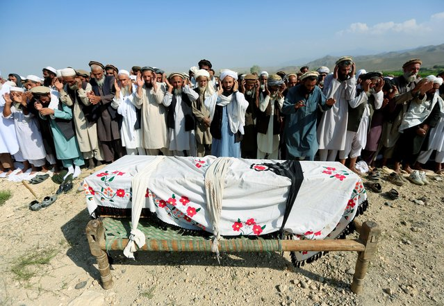Relatives and residents pray near a coffin during a funeral ceremony of one of the victims after a drone strike, in Khogyani district of Nangarhar province, Afghanistan September 19, 2019. A U.S. drone strike intended to hit an Islamic State hideout in Afghanistan killed at least 30 civilians resting after a day's labor in the fields, officials said on Thursday. (Photo by Parwiz via Reuters)
