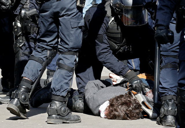 French gendarmes apprehend a demonstrator during clashes at the traditional May Day labour union march in Paris, France on May 1, 2017. (Photo by Gonzalo Fuentes/Reuters)