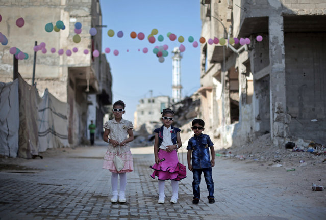 Palestinians Sajeda Areir, 8, left, her sister Farah,7, center, and their brother Mohammed pose for a photograph as they dressed up to celebrate the first day of Eid al-Fitr in the Shijaiyeh neighborhood of Gaza City, Friday, July 17, 2015. (Photo by Khalil Hamra/AP Photo)