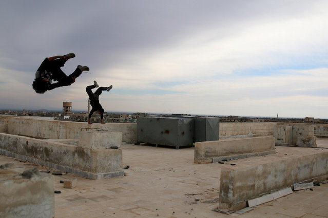 "Parkour coach Ibrahim al-Kadiri, 19, demonstrates his Parkour skills with his friend in the rebel-held city of Inkhil, west of Deraa, Syria, February 4, 2017. Ibrahim says many team members suffered injuries, including broken toes and bruises. He himself injured his back: ""Eight months ago, during an attempt to jump from high place, I injured my back and I stayed in bed for several days until I recovered"". (Photo by Alaa Al-Faqir/Reuters)"
