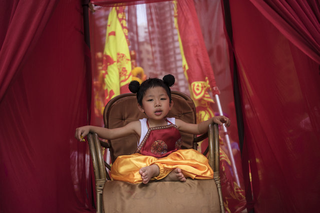 A child sitting on a chair during the Buddha's Birthday festival in Shau Kei Wan, Hong Kong, on May 3, 2017. (Photo by Chan Long Hei/Pacific Press/LightRocket via Getty Images)