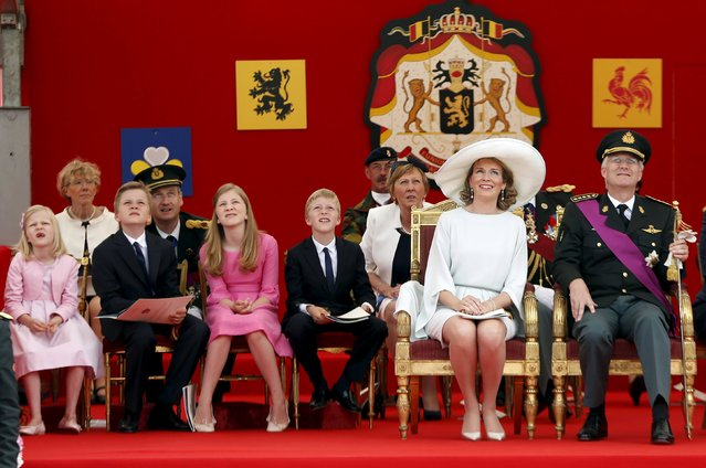Belgium's King Philippe (R) and Queen Mathilde (2nd R) watch the traditional military parade with their children Princess Eleonore, Prince Gabriel, Crown Princess Elisabeth and Prince Emmanuel (front row, L-3rd R) in front of the Royal Palace in Brussels July 21, 2015. (Photo by Francois Lenoir/Reuters)