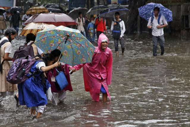 Indian school children hold hands as they walk through a water logged street as it rains in Mumbai, India, Tuesday, July 21, 2015. Heavy rainfall threw normal life out of gear in the city Tuesday, leading to water logging in low-lying areas, disrupting local train services and causing traffic havoc. (Photo by Rajanish Kakade/AP Photo)