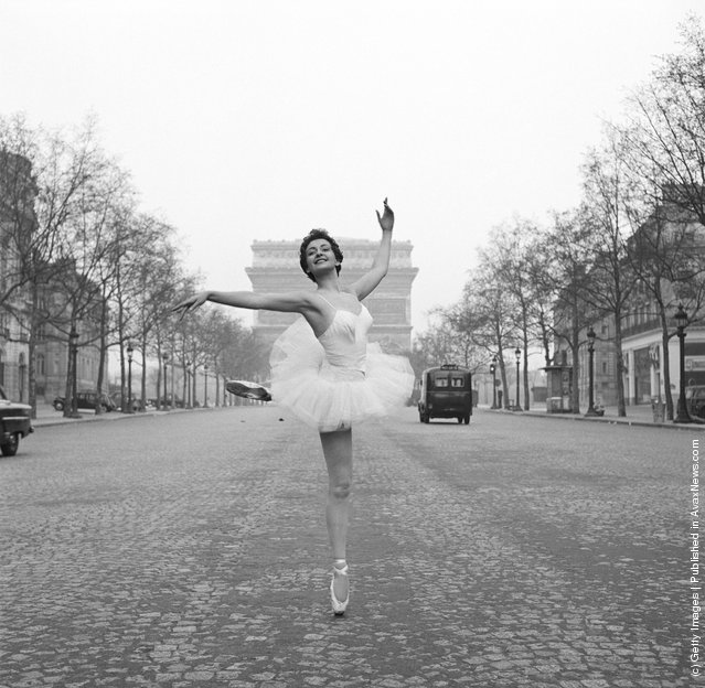 Ballerina Christianne Gaulthier, a dancer at the Moulin Rouge, fulfils a lifelong dream - to dance through the deserted streets of Paris at the crack of dawn, 1955. Here she assumes a classic ballet position on the Champs Elysees