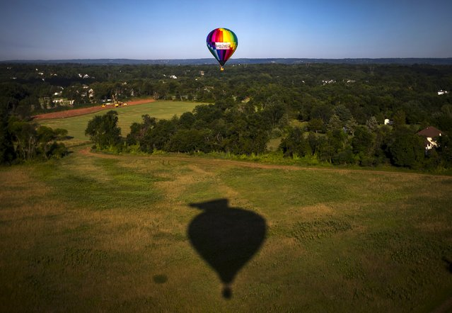A hot air balloon and a shadow of another is seen from a flying balloon above a farm field during a flight just after sunrise on day one of the 2015 New Jersey Festival of Ballooning in Readington, New Jersey, July 24, 2015. (Photo by Mike Segar/Reuters)