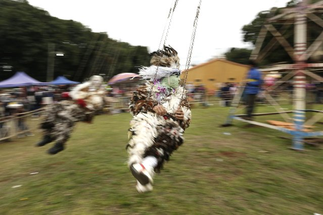 A Catholic faithful dressed in a bird-feather suit, flies past on a chair swing ride during the feast day celebrations for St. Francisco Solano, in Emboscada, Paraguay, Friday, July 24, 2015. The parish priest says the festivity became a tradition because the birthday of Francisco Solano Lopez, the son of 19th century Paraguayan President Carlos Antonio Lopez, fell on Saint Francis' feast day. The Paraguayan president served from 1841 to 1862. (Photo by Jorge Saenz/AP Photo)