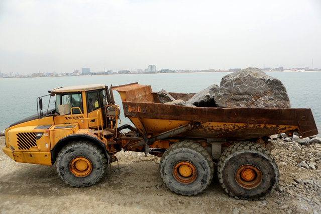 A constuction worker waits to lower rocks into water, where land reclaimation is taking place, as part of the Eko Atlantic city development project in Lagos, Nigeria, May 28, 2016. (Photo by Joe Penney/Reuters)