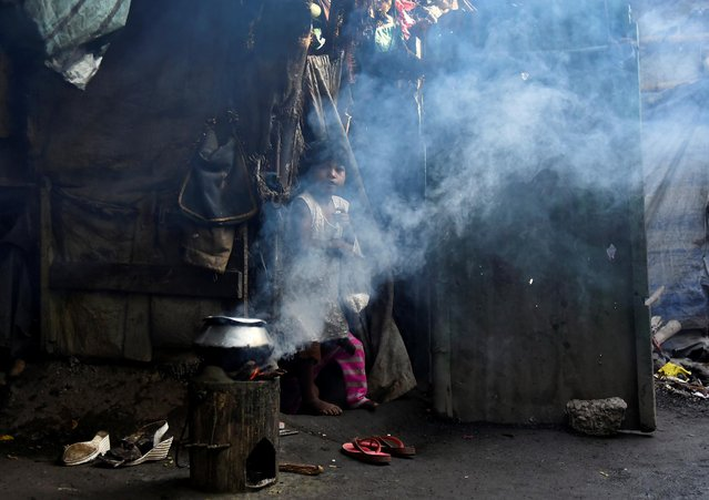 A girl looks on as smoke billows from a wood fired cauldron outside her hut in Howrah on the outskirts of Kolkata, November 19, 2019. (Photo by Ranita Roy/Reuters)