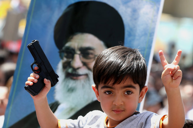 An Iraqi boy living in Iran holds a toy gun and flashes a victory sign in front of a poster of the Iranian Supreme leader Ayatollah Ali Khamenei in a demonstration against Sunni militants of the al-Qaida-inspired Islamic State of Iraq and the Levant, or ISIL, and to support the Grand Ayatollah Ali al-Sistani, Iraq's top Shiite cleric, in Tehran, Iran, Friday, June 20, 2014. (Photo by Ebrahim Noroozi/AP Photo)
