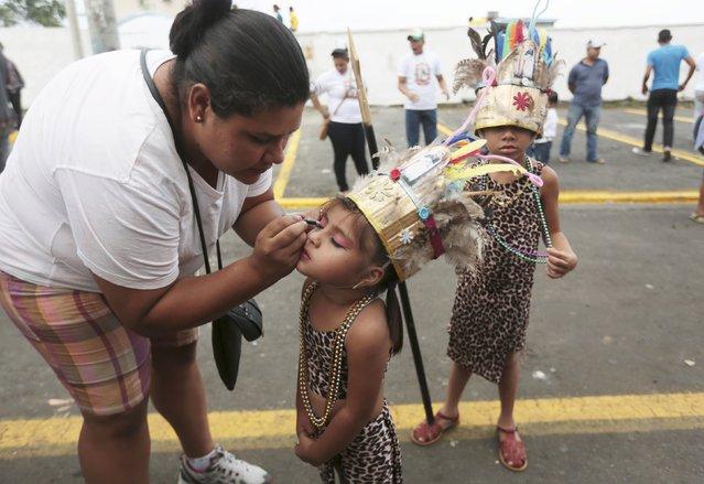 A woman applies makeup to the face of her daughter during celebrations honouring the patron saint of Managua, Santo Domingo de Guzman, in Managua, Nicaragua July 31, 2015. (Photo by Oswaldo Rivas/Reuters)