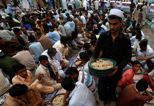 A volunteer distributes plates of boiled rice with beef and potatoes to people gathering to break their fast during the Muslim holy month of Ramadan in Karachi, Pakistan, June 8, 2016. (Photo by Akhtar Soomro/Reuters)