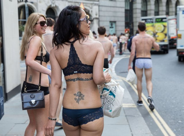A flashing flashmob paraded around central London in their underwear in a protest over bank charges, on June 13, 2014. The semi-naked gang stripped down to their bras and briefs – giving morning commuters an eyeful. The scantily clad protesters stunned passengers at Liverpool Street Station and were also spotted in Angel, Farringdon and Kings Cross Square. More than 100 daring campaigners turned out for the event – which luckily coincided with the warmest day of the year so far. (Photo by Jeff Moore)