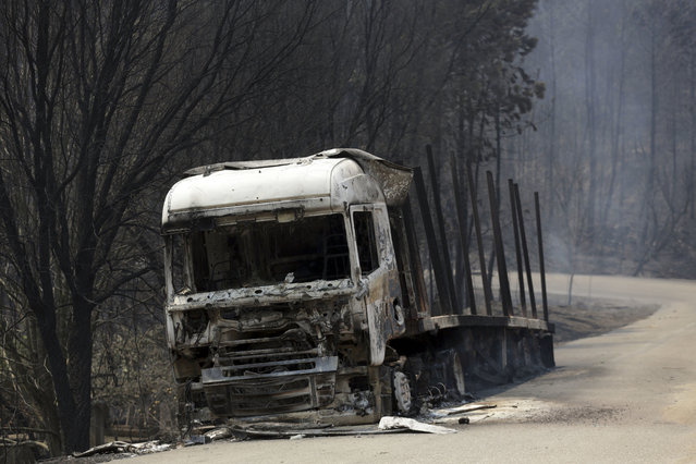 A burnt truck lies on a dirt road close to the road between Castanheira de Pera and Figueiro dos Vinhos, central Portugal, Sunday, June 18 2017. Raging forest fires in central Portugal killed at least 50 people, many of them trapped in their cars as flames swept over a road Saturday evening. (Photo by Armando Franca/AP Photo)