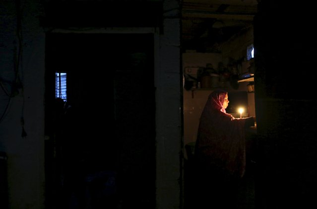 A Palestinian woman does the washing-up by a candle light at her kitchen during a power cut in the northern Gaza Strip March 25, 2015. (Photo by Mohammed Salem/Reuters)