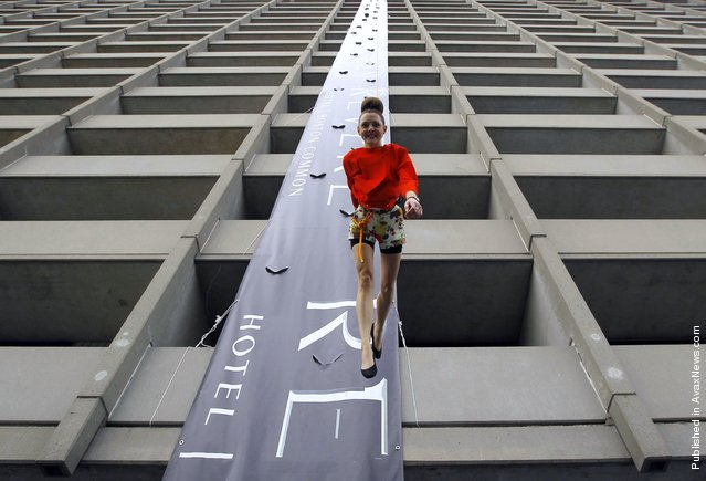A model walks down the side of Revere Hotel in Boston during a vertical fashion show for the Massachusetts College of Art and Design