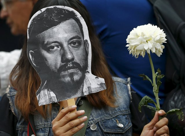 An activist holds up a picture of photojournalist Ruben Espinosa during a protest against his murder at the Angel of Independence monument in Mexico City, Mexico August 2, 2015. The prominent Mexican news photographer was among five people found dead in a middle-class neighborhood of the capital on Friday, the city's prosecutor said on Sunday. (Photo by Henry Romero/Reuters)
