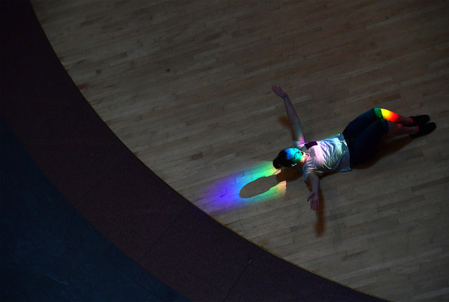 Caitlin Jackson, 24, lays in a rainbow pattern created by the sun passing through prisms as she is photographed by her mother, Carla McGowan at the National Museum of the American Indian on Tuesday June 20, 2017 in Washington, DC. Wednesday June 21st is the summer solstice. (Photo by Matt McClain/The Washington Post)