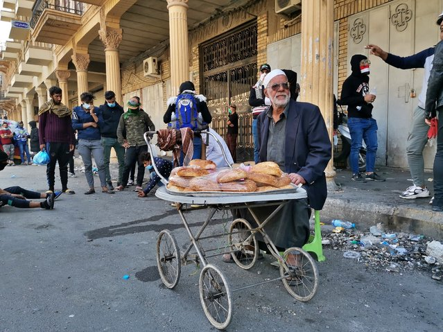 In this Tuesday, November 26, 2019 photo, a street vendor sells cakes on Rasheed Street in Baghdad, Iraq. Baghdad's Rasheed Street was the scene of large marches by Iraqis against British occupiers nearly a century ago and now it's a front line in a new revolt. (Photo by Hadi Mizban/AP Photo)