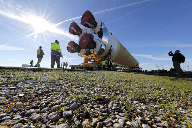 Security and safety personnel walk with the core stage of NASA's Space Launch System rocket, that will be used for the Artemis 1 Mission, as it is moved to the Pegasus barge, at the NASA Michoud Assembly Facility where it was built, in New Orleans, Wednesday, January 8, 2020. It will be transported to NASA's Stennis Space Center in Mississippi for its green run test. (Photo by Gerald Herbert/AP Photo)