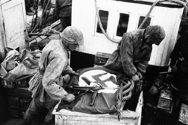 To alert their own airforce to their presence, soldiers spread the Swastika across boats used by the S.S. troops to cross the Gulf of Corinth, Greece, on May 23, 1941