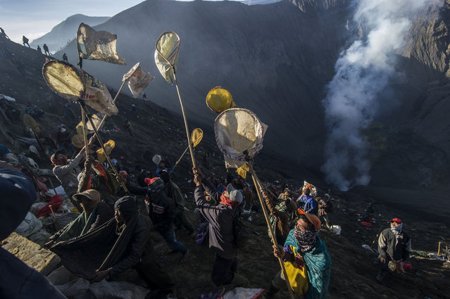 Indonesian villagers catch money and live offerings thrown by members of the Tengger tribe into the crater of mount Bromo volcano during the Yadnya Kasada Festival in Probolinggo on July 10, 2017. Members of the Tengger tribe who live around mount Bromo-Semeru volcano throw live offerings into the crater to honour Sang Hyang Widhi, God Almighty, on the 14th day of the Kasada Month based on the traditional Hindu lunar calendar. (Photo by Juni Kriswanto/AFP Photo)