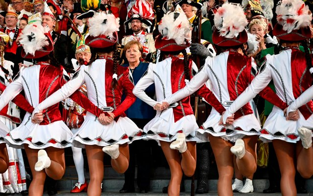 German Chancellor Angela Merkel (C) watches a performance of a carnival dance group as she poses with members of carnival orders during a reception on January 22, 2020 at the Chancellery in Berlin. (Photo by Tobias Schwarz/AFP Photo)