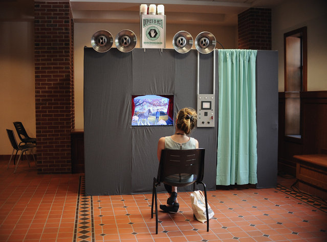 """Kristin Haverty, of Atlanta, watches a personalized puppet show at the """"Depict-o-Mat"""" booth while attending at the National Puppetry Festival at the University of Connecticut, Monday, August 10, 2015, in Storrs, Conn. Puppeteers from around the world began descending on UConn Monday to participate in the weeklong festival of all things puppet. (Photo by Jessica Hill/AP Photo)"""