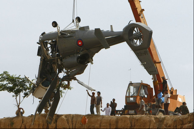 Soldiers use a crane to lift an aft section of a helicopter retrieved from a pond following its crash in Prey Sar village at the outskirt of Phnom Penh, Cambodia, Monday, July 14, 2014. The chopper went down about 10 kilometers (6 miles) south of Phnom Penh on Monday, sinking in a muddy pond surrounded by rural land and rice fields. (Photo by Heng Sinith/AP Photo)