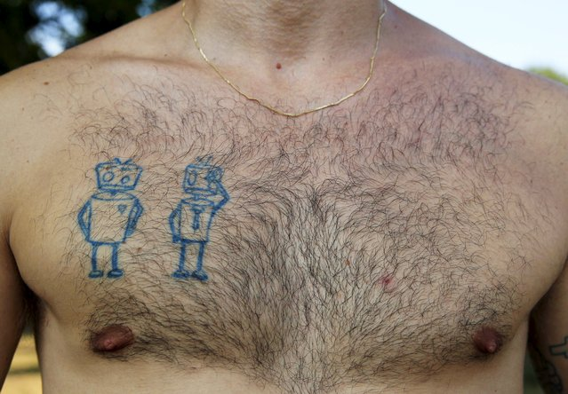 Alexander Koko, 35, from Russia shows his tattoo during the Sziget music festival on an island in the Danube River in Budapest, Hungary, August 14, 2015. (Photo by Bernadett Szabo/Reuters)