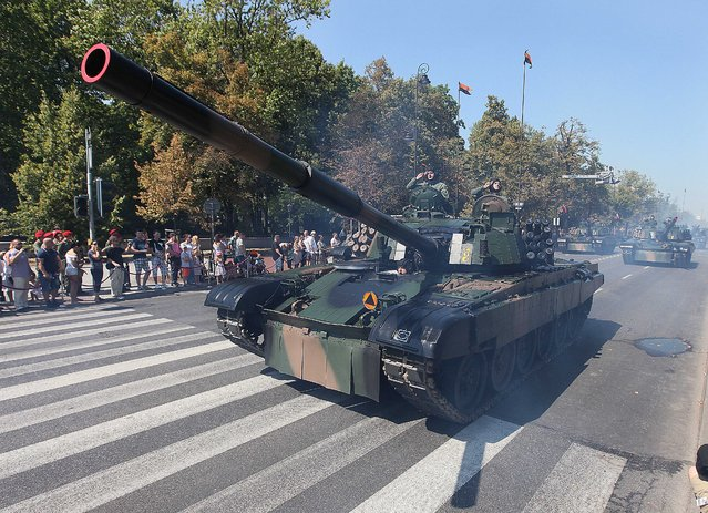 Polish army soldiers salute as tanks roll on one of the city's main streets during a military parade celebrating the Polish Army Day in Warsaw, Poland, Saturday, August 15, 2015. (Photo by Czarek Sokolowski/AP Photo)