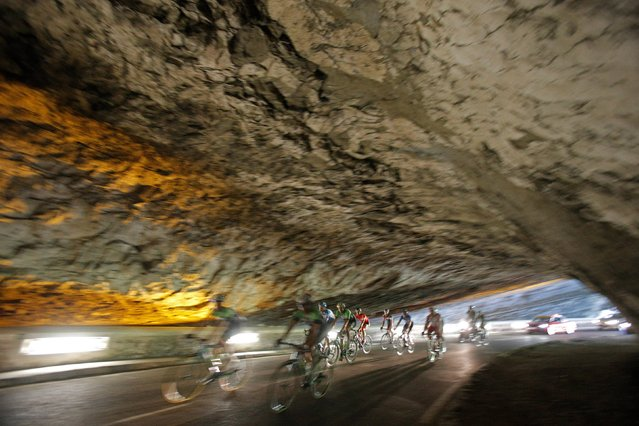 The pack rides through a tunnel during the sixteenth stage of the Tour de France cycling race over 237.5 kilometers (147.6 miles) with start in Carcassonne and finish in Bagneres-de-Luchon, France, Tuesday, July 22, 2014. (Photo by Christophe Ena/AP Photo)