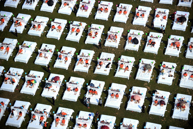 A picture made available on 18 August 2015, shows people having breakfast in beds in an effort to set a new Guinness World Record in Beijing, China, 16 August 2015. A total of 418 people paticipated in the challenge of the record of the most people having breakfast in bed at the same time. (Photo by Lao Cai/EPA)