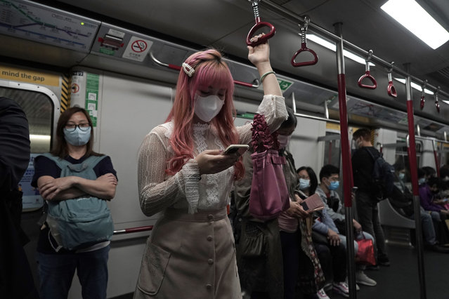 A woman wearing a face mask as a precaution against the COVID-19 while using smartphone in a subway train in Hong Kong, Thursday, February 27, 2020. As the worst-hit areas of Asia continued to struggle with a viral epidemic, with hundreds more cases reported Thursday in South Korea and China, worries about infection and containment spread across the globe. (Photo by Kin Cheung/AP Photo)
