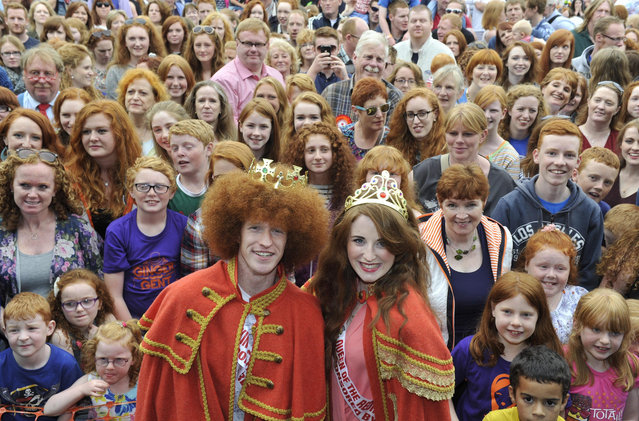 Newly crowned Redhead King and Queen, Alan Reidy and Grainne Keena pose with a crowd full of red heads at the Irish Redhead Convention which celebrates everything to do with red hair held in the village of Crosshaven on August 22, 2015 in Cork, Ireland. Some of the events include the coronation of the Redhead King and Queen, Carrot-tossing, ginger speed-dating, best red beard, best red dog, freckle counting and a redhead parade. (Photo by Clodagh Kilcoyne/Getty Images)