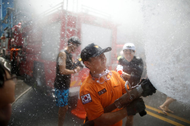 A firefighter sprays water on participants during the Sinchon Water Gun Festival in Seoul, South Korea, July 9, 2016. (Photo by Kim Hong-Ji/Reuters)
