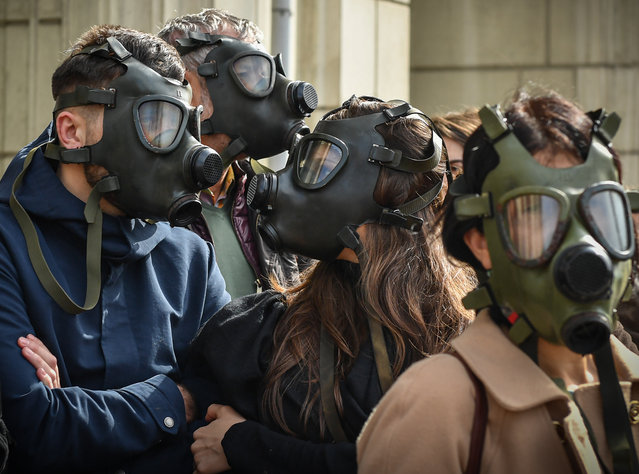 "Protesters wear gas masks in the front of the Romanian Environment Ministry in Bucharest March 4, 2019, to demand better air. Dozens of people holding placards reading ""Our children don't breath air anymore"" gather in the front of the Environment Ministry to ask for better breathable air in Bucharest. (Photo by Daniel Mihailescu/AFP Photo)"
