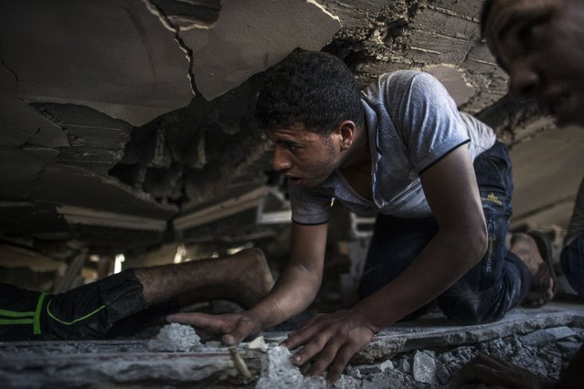 Palestinian men crawl under the rubble of a house looking for survivors after it was hit by an Israeli air strike on the al-Shati refugee camp in Gaza City on August 4, 2014. Israel was observing a temporary unilateral truce in most of the Gaza Strip amid world outrage over a deadly strike on a UN school in the besieged Palestinian territory. (Photo by Marco Longari/AFP Photo)