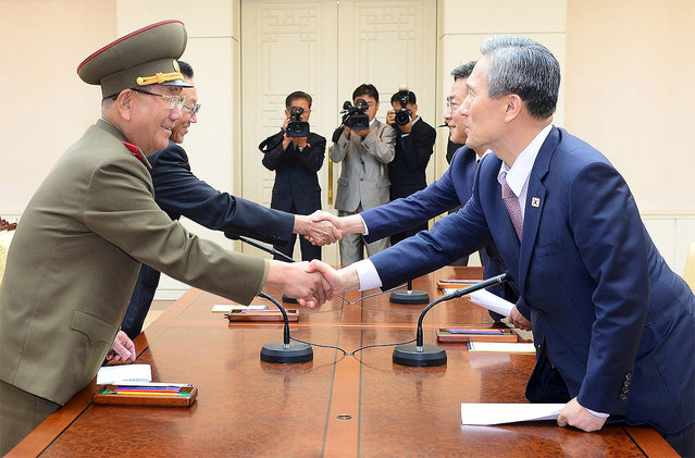 South Korean National Security Adviser Kim Kwan-jin (R), South Korean Unification Minister Hong Yong-pyo (2nd R), Secretary of the Central Committee of the Workers' Party of Korea Kim Yang Gon (2nd L), and Hwang Pyong-so (L), the top military aide to the North's leader Kim Jong Un,  shake hands after the inter-Korean high-level talks at the truce village of Panmunjom inside the Demilitarized Zone separating the two Koreas, in this picture provided by the Unification Ministry and released by Yonhap on August 25, 2015. (Photo by Reuters/Yonhap/The Unification Ministry)
