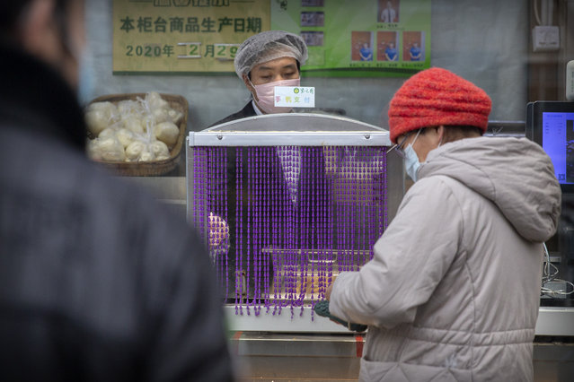 """A clerk wears a face mask as he waits for a customer to pay at a bakery in Beijing, Saturday, February 29, 2020. The coronavirus outbreak's impact on the world economy grew more alarming on Saturday, even as President Donald Trump denounced criticisms of his response to the threat as a """"hoax"""" cooked up by his political enemies. (Photo by Mark Schiefelbein/AP Photo)"""