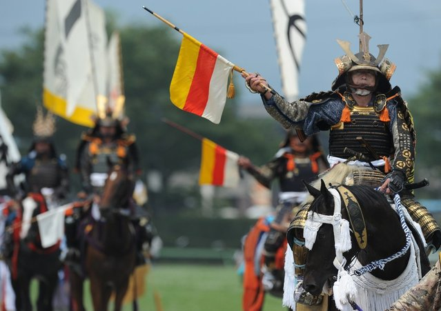 """Local people in samurai armor ride their horses during a parade at the annual Soma Nomaoi Festival in Minamisoma, Fukushima Prefecture, on July 29, 2012. Some 400 horses and thousands of people took part in the 1,000-year-old """"Soma Nomaoi"""", or wild horse chase, at the weekend in the shadow of Japan's crippled Fukushima nuclear plant. (Photo by Toru Yamanaka/AFP Photo)"""