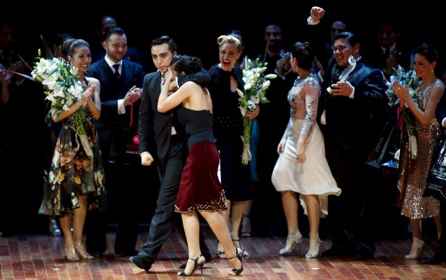 Jonathan Saavedra (L) and Clarisa Aragon from Argentina,  who are representing the Argentine city of Cordoba, embrace after winning the Tango World Championship in Salon style as other couples cheer, in Buenos Aires August 26, 2015. (Photo by Marcos Brindicci/Reuters)