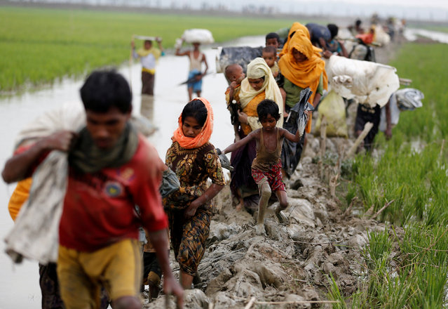 Rohingya refugees walk on the muddy path after crossing the Bangladesh-Myanmar border in Teknaf, Bangladesh, September 3, 2017. (Photo by Mohammad Ponir Hossain/Reuters)