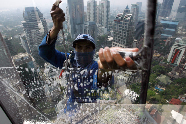 A worker cleans the window of a building in Bangkok January 22, 2009. (Photo by Sukree Sukplang/Reuters)