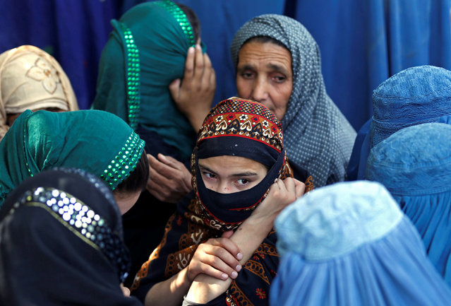 Afghan women wait to receive aid from the Afghanistan Chamber of Commerce and Industries during the month of Ramadan in Kabul, Afghanistan June 23, 2016. (Photo by Mohammad Ismail/Reuters)