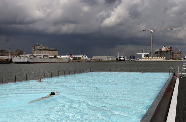 """Swimmers enjoy a floating open-air swimming pool called """"badboot"""" in the port of Antwerp August 20, 2014. The venue is located in a 120 metre-long (394 feet) former barge which can accommodate 600 people and consists of two swimming pools, two event venues and a restaurant with a lounge terrace. (Photo by Francois Lenoir/Reuters)"""