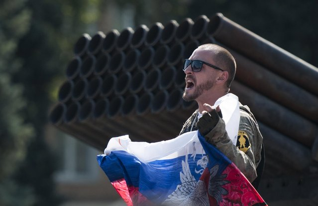 A pro-Russian rebel holds a Russian national flag near to damaged heavy hardware from the Ukrainian army during an exhibition in the central square in Donetsk, eastern Ukraine, Sunday, August 24, 2014. Ukraine has retaken control of much of its eastern territory bordering Russia in the last few weeks, but fierce fighting for the rebel-held cities of Donetsk and Luhansk persists. (Photo by Antoine E.R. Delaunay/AP Photo)