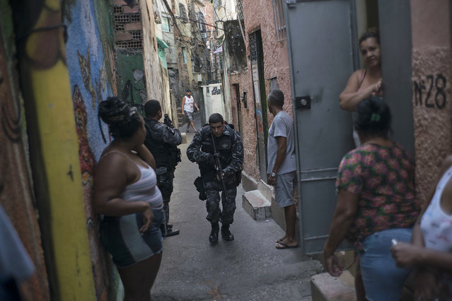 """In this June 29, 2016 photo, a police officer patrols among residents during an operation against drug traffickers at the """"pacified"""" Jacarezinho slum in Rio de Janeiro, Brazil. The Pacification Police Units, known by the Portuguese acronym UPP, were created in 2008, setting up community stations in at-risk areas, mostly near sports venues, posh tourist districts and downtown. A drug gang leader called the program a """"facade"""". He said that drug dealers were initially worried and kept a low profile, but soon it was back to business as usual. (Photo by Felipe Dana/AP Photo)"""